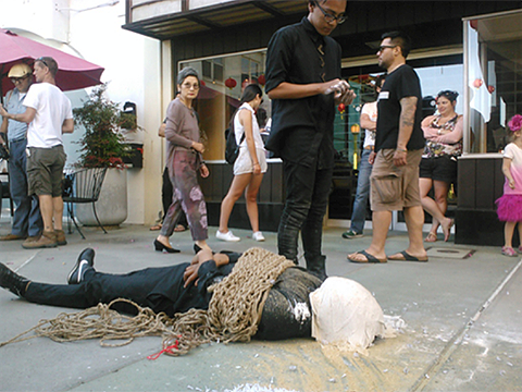 Performance art, a man lies on the sidewalk with a bag over his head and heavy ropes tied around his body.