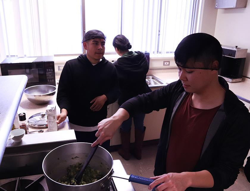 Students cooking vegetables in the food lab.