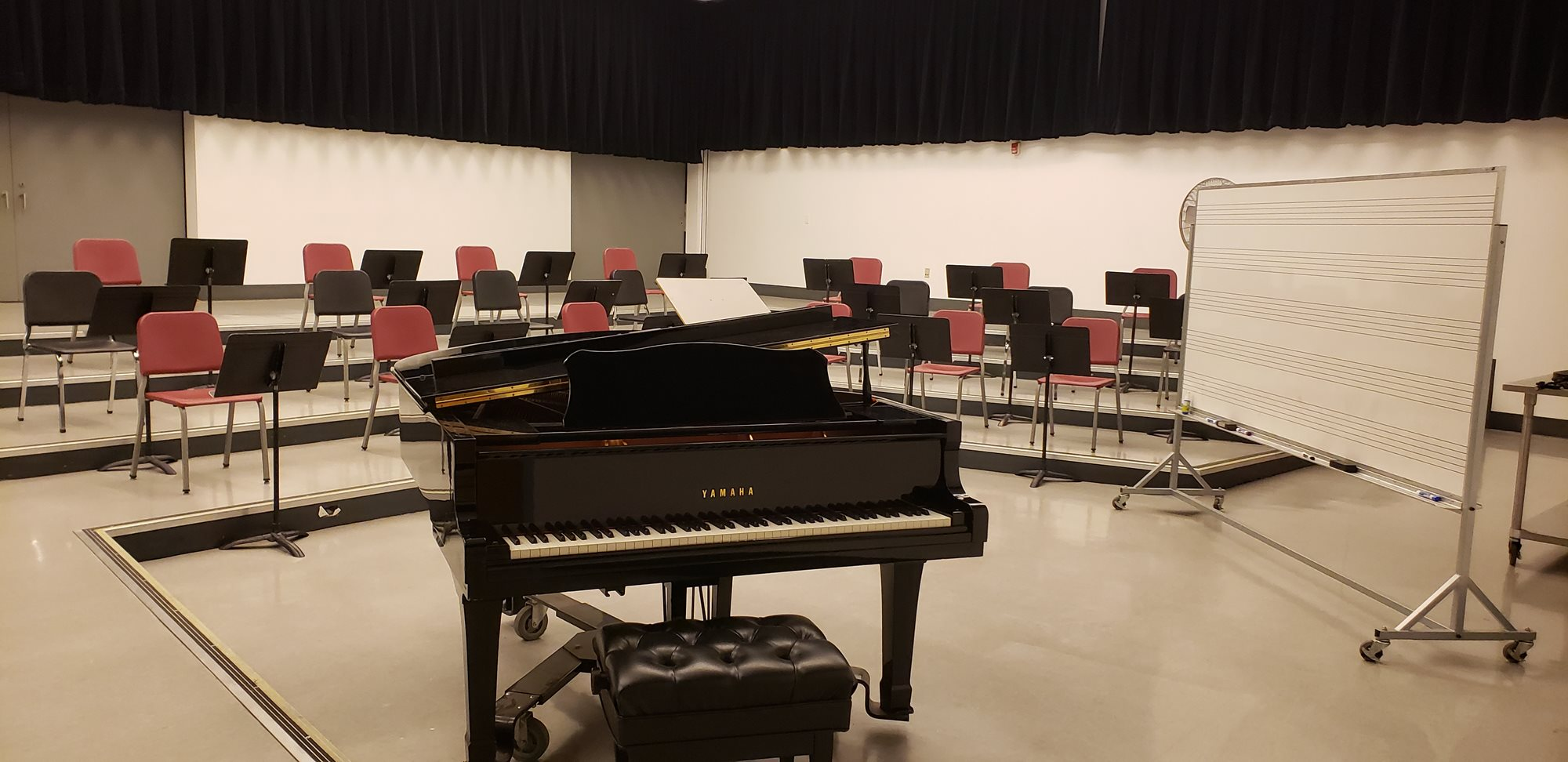 An open piano sits in front of several rising rows of chairs and music stands.