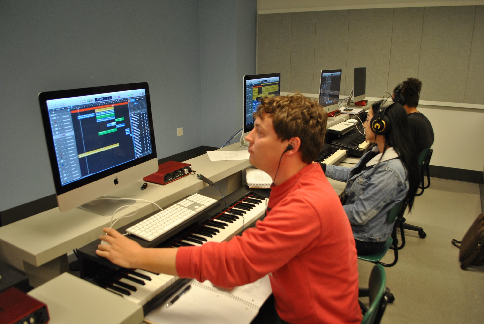A student operates a computer in front of a MIDI keyboard, running digital audio software.
