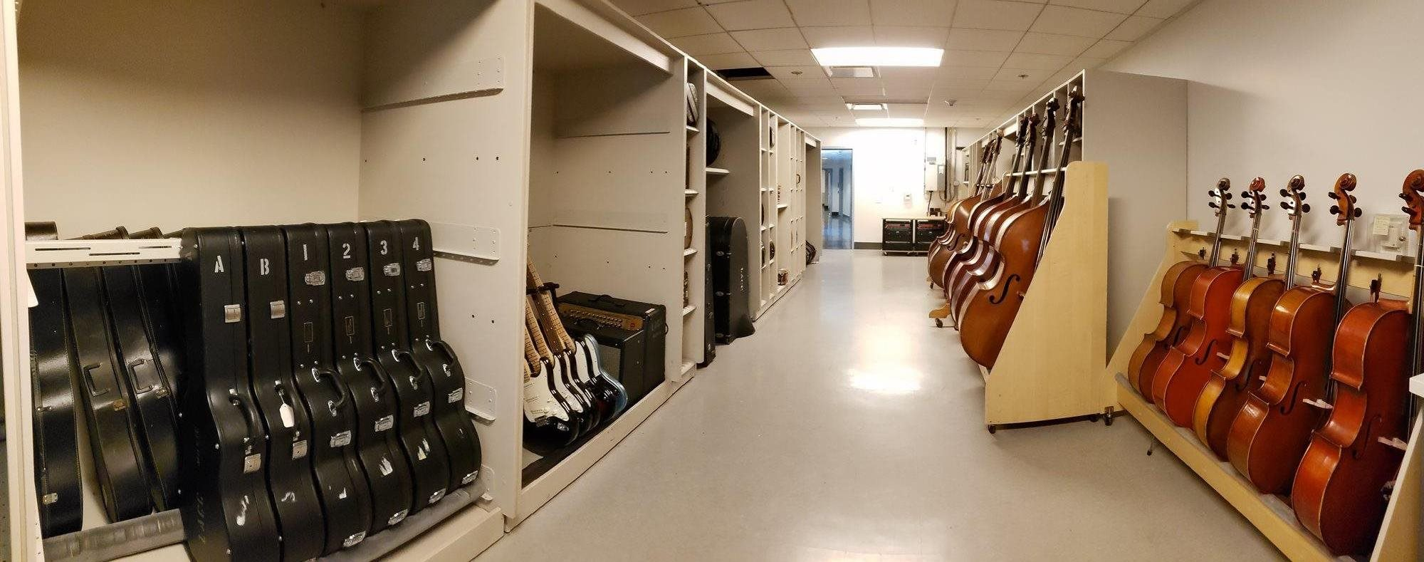 A long room, the walls lined with basses, cellos, guitars, and wind and brass instrument cases.