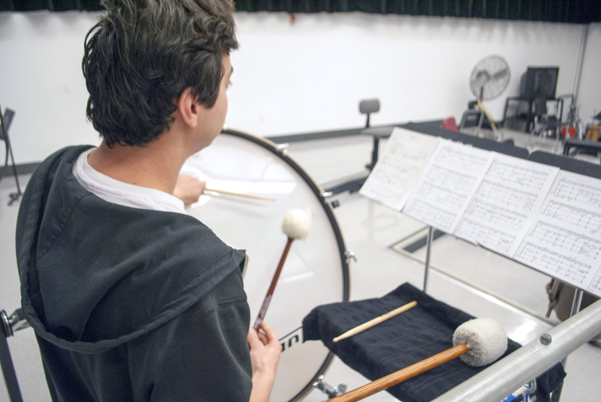A student plays bass drum in front of several pages of sheet music.