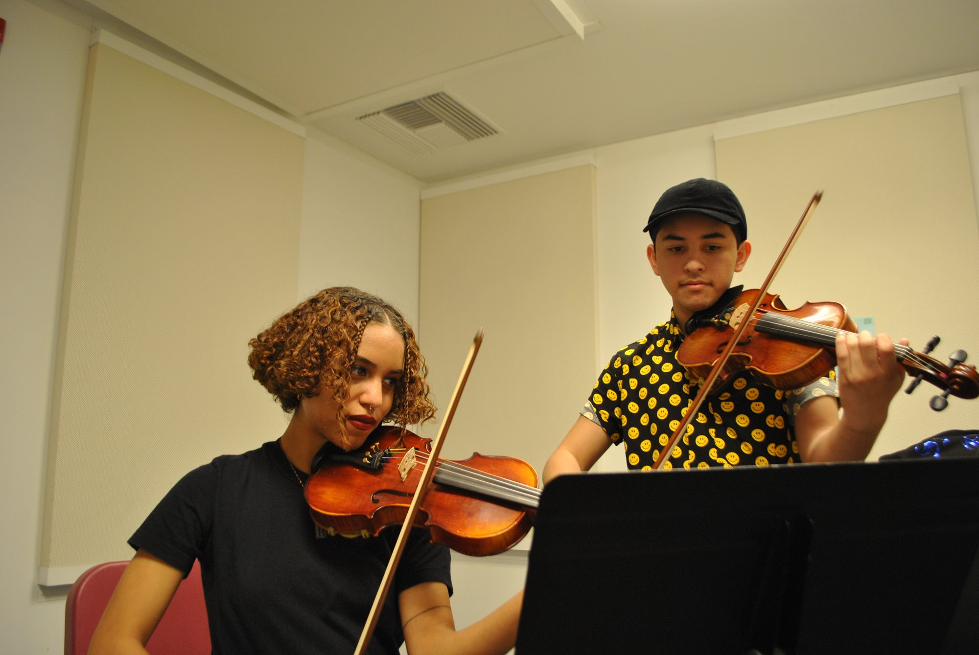 Two students play violin together.
