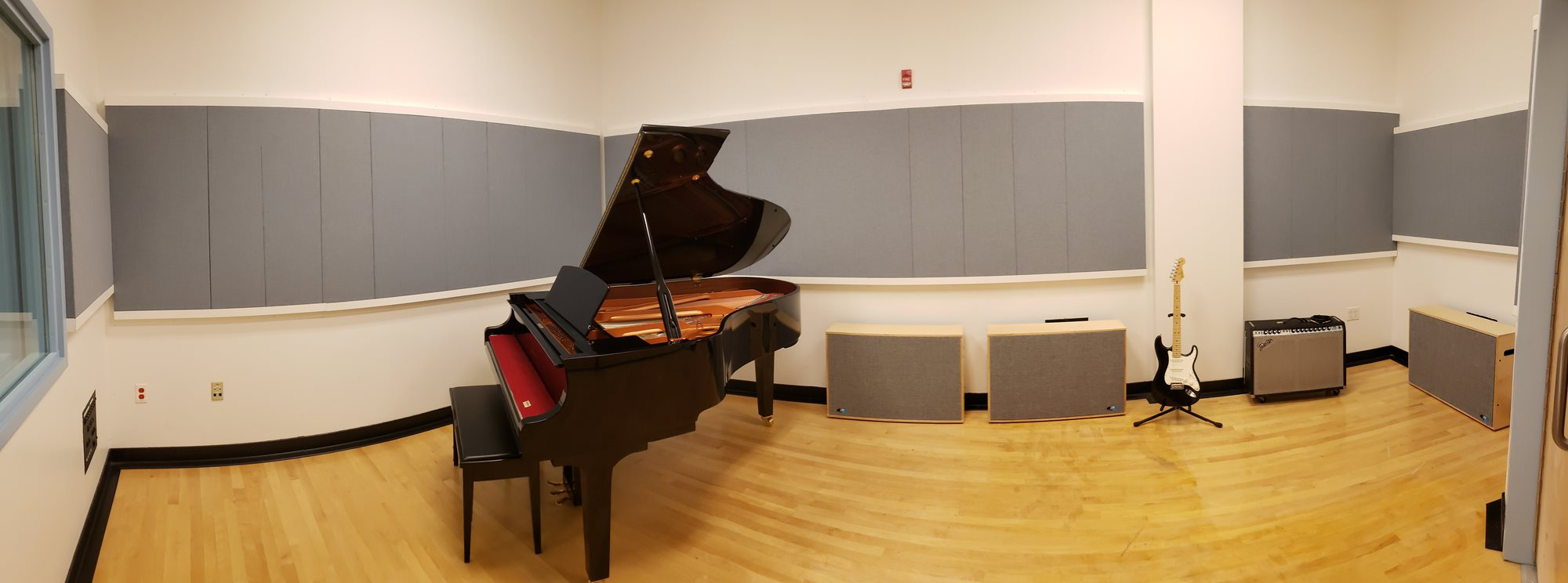 A panoramic display of our tracking room containing an open baby grand piano, a guitar, and an amplifier.