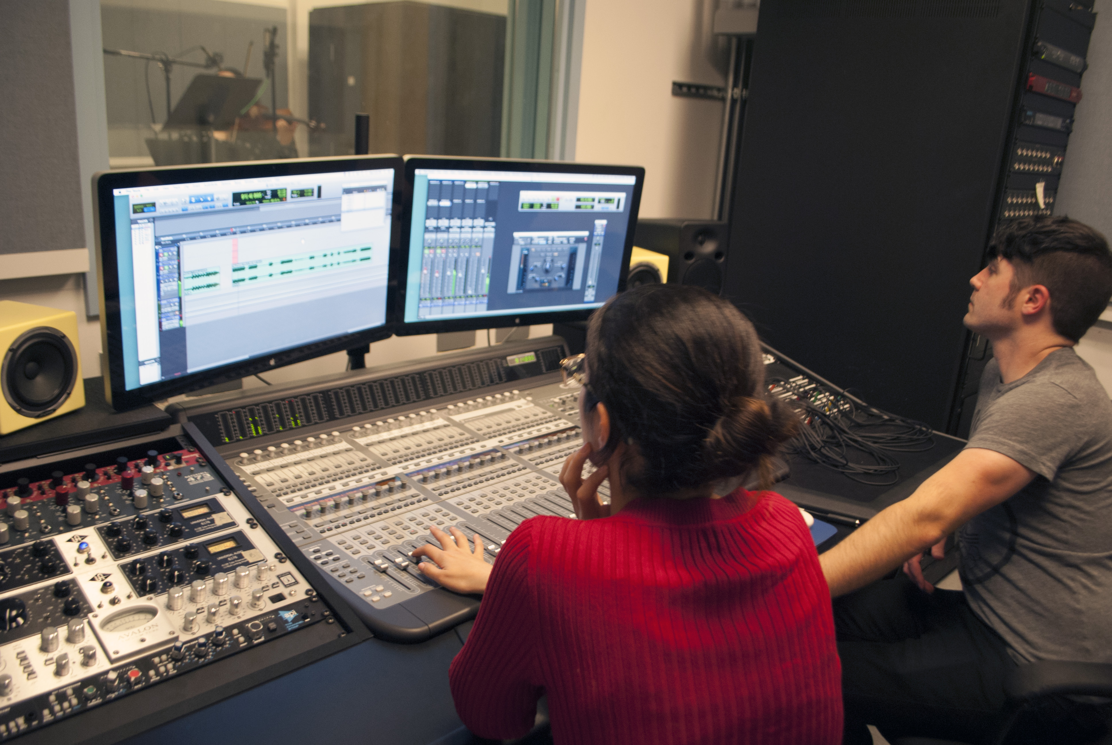 Students operating the control room console and Pro Tools rig in our Recording Studio.