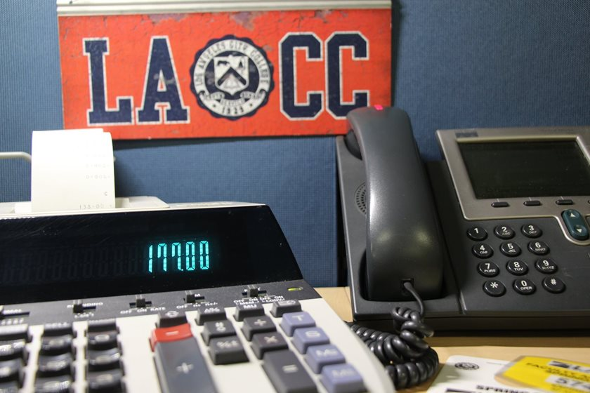 A calculator and parking pass are arranged on a desk below a vintage LACC banner.