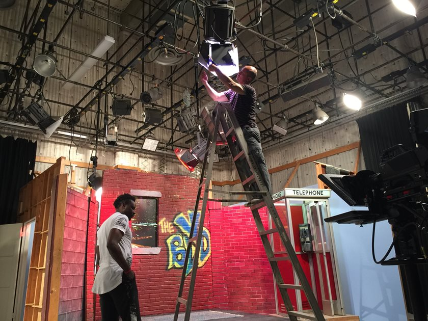 Students hanging lights in the Dick Clark studios